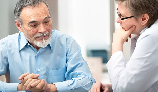 Older man talking with his doctor.