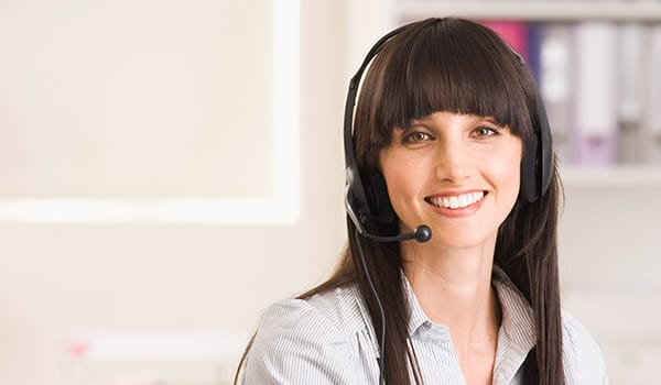 Young woman smiling and wearing phone headset.